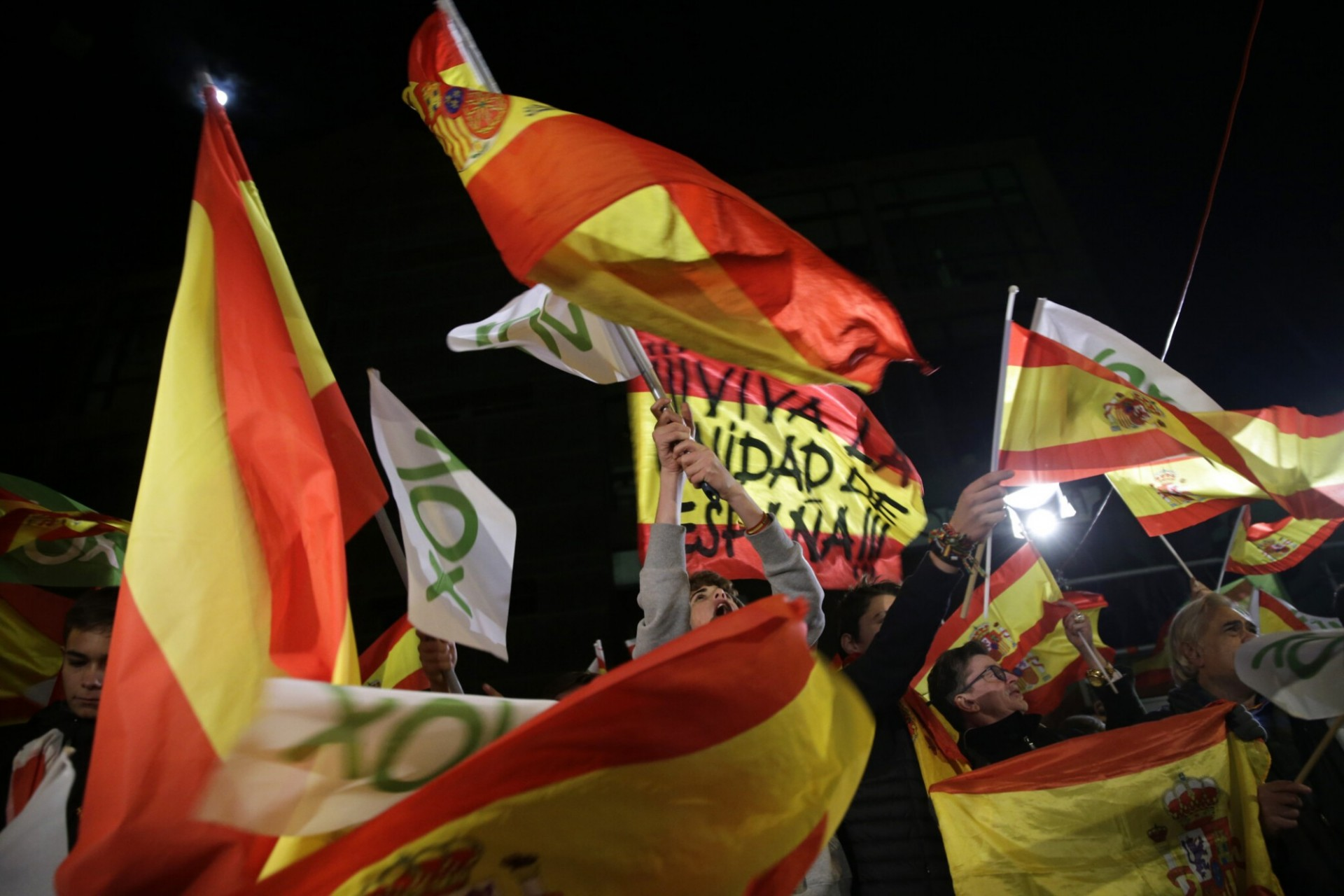 A crowd waves flags for Spain and its far-right Vox party