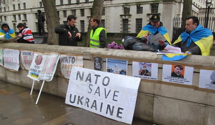 "People behind a wall posted with signs, with one sign prominently stating ""NATO save Ukraine"""