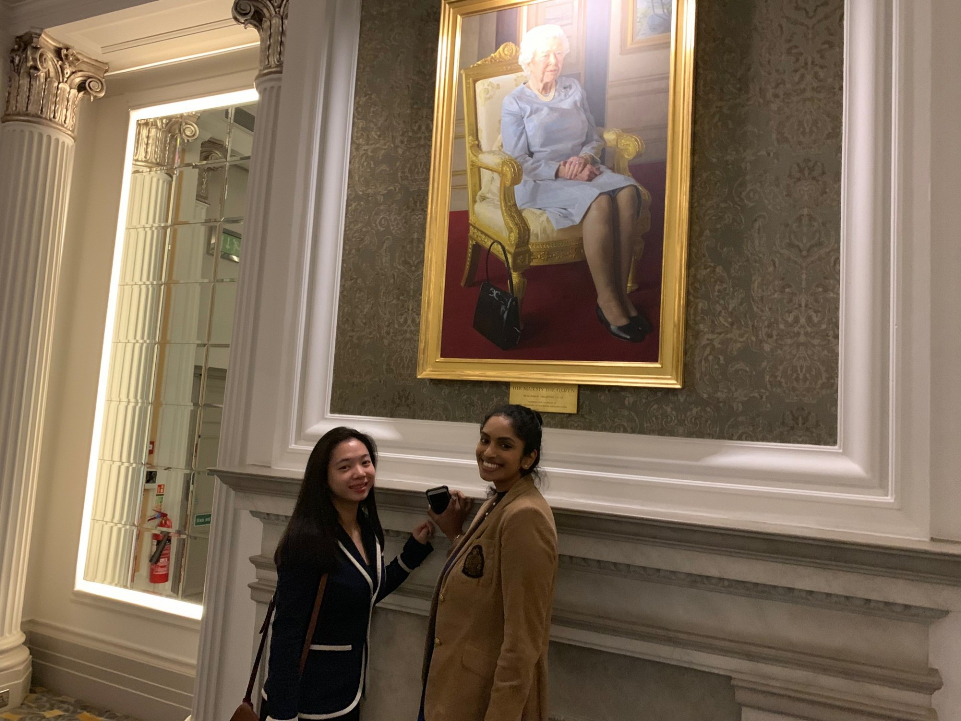 CWAR Fellows Celeste Chan and Sreya Pinnamaneni pose in front of a painting of Queen Elizabeth II at the Royal Air Force Club
