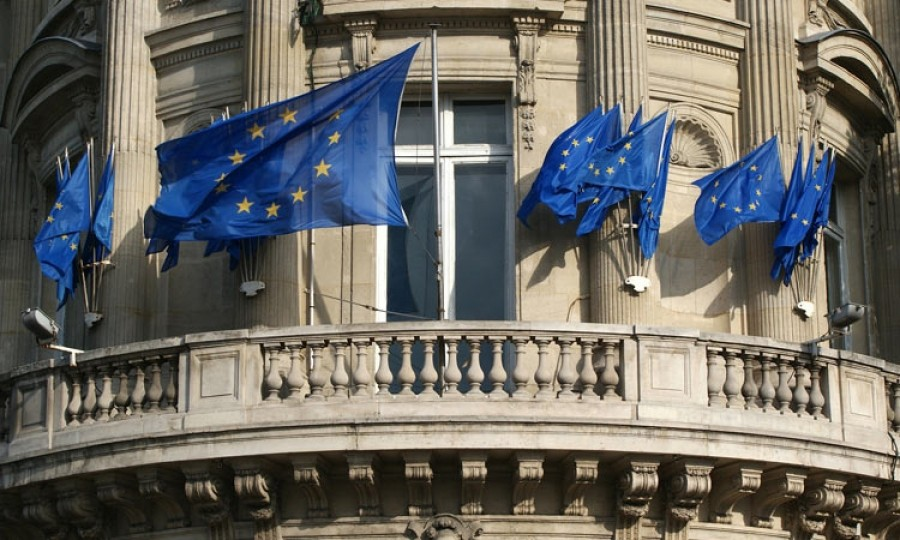 Image of several EU flags on a building balcony